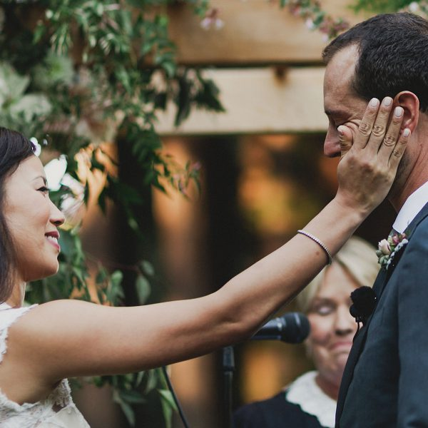 touching moment of a bride wiping her groom's tear away during their wedding ceremony at the Mountain Terrace by Heather Elizabeth Photography