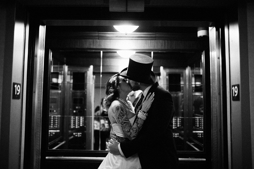 Tattooed alternative bride and her groom in a top hat kiss in the closing elevator of the Hilton in San Francisco