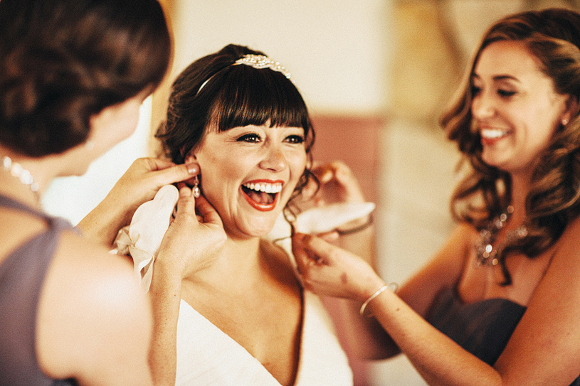 Bride laughing as her earrings are put on by her bridesmaids before her wedding