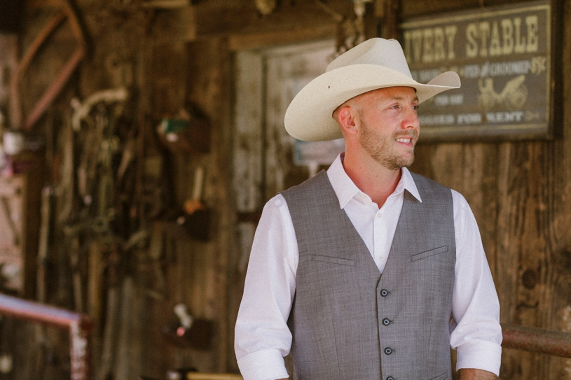cowboy groom at his farmhouse wedding by Heather elizabeth photography