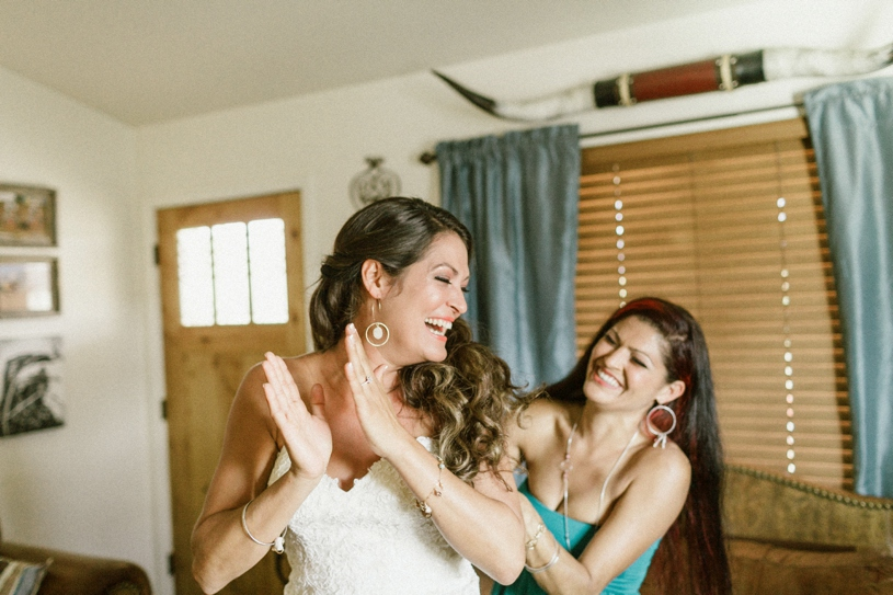 Bride getting her dress put on by her best friend at her farm house wedding by heather elizabeth photography
