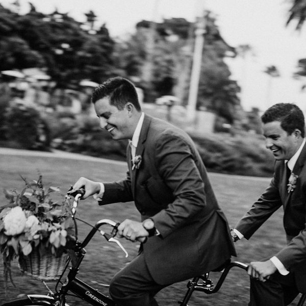 Groom and Groomsmen riding a vintage bike at his wedding at the Four Seasons in Santa Barbara by Heather Elizabeth Photography