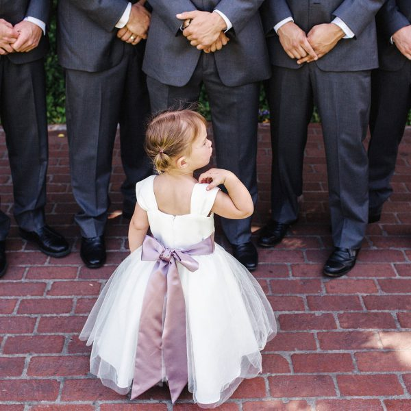 A sweet flowergirl looking at the groomsmen at a wedding at the Four Seasons in Santa Barbara by Heather Elizabeth Photography
