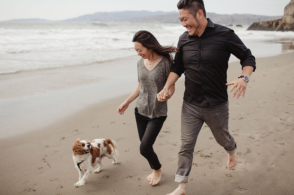 A couple during their engagement session with their dog at the Sutro Bath's by Heather Elizabeth Photography in San Francisco
