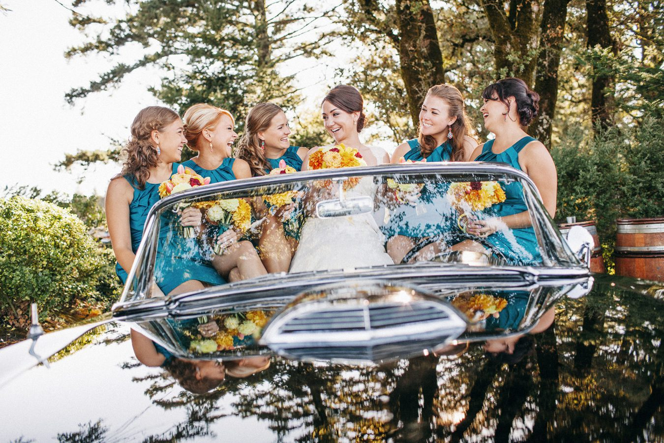 A teal and orange bridal party posing on a Classic Ford Thunderbird at the Thomas Fogarty Winery by Heather Elizabeth Photography
