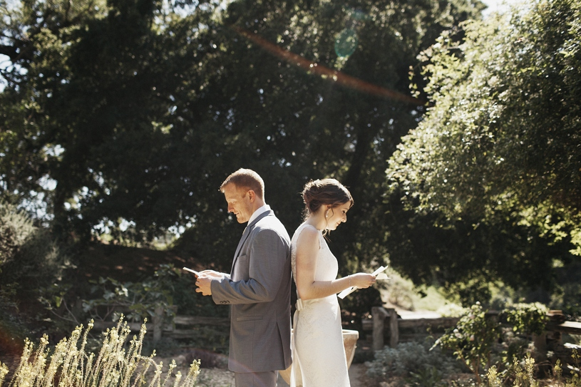 bride and groom reading each other letter's before their first look at the putah creek lodge in uc davis by heather elizabeth photography