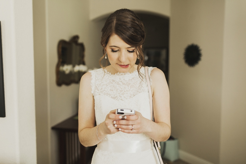 photo journalism of bride texting during her wedding at UC Davis by Heather Elizabeth Photography