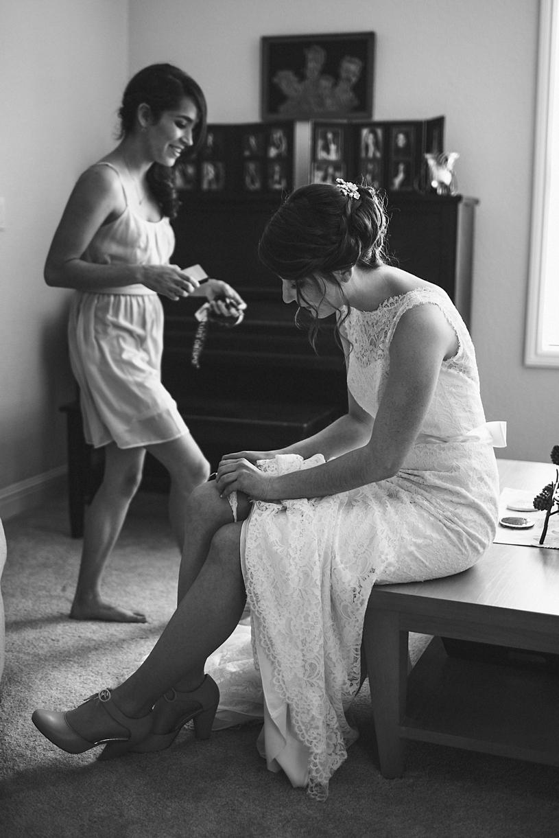 photo journalism of bride putting on her garter at a wedding in UC davis by heather elizabeth photography