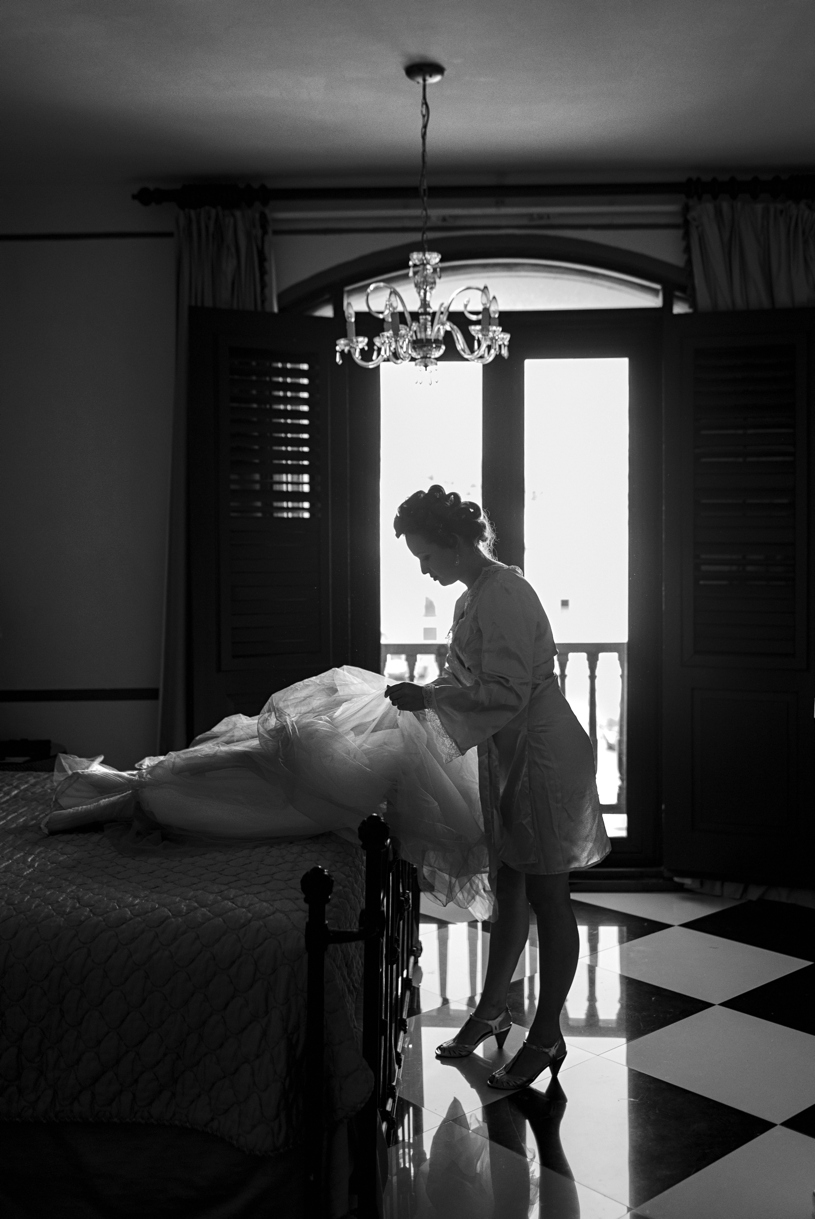 Bride preparing her dress in the bride suite of the el hotel convento in old san juan puerto rico by heather elizabeth photography