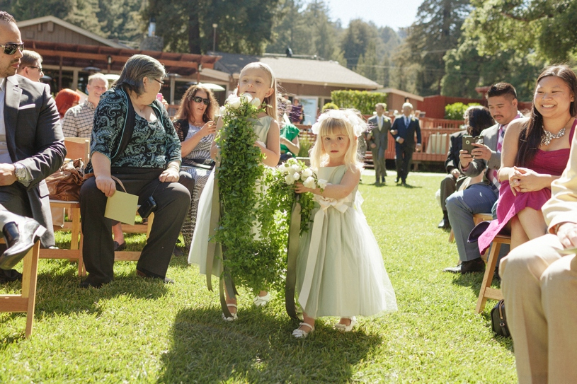 Flower girls bringing green heavy florals down the aisle together during an eco friendly organic wedding at the mountain terrace by heather elizabeth photography