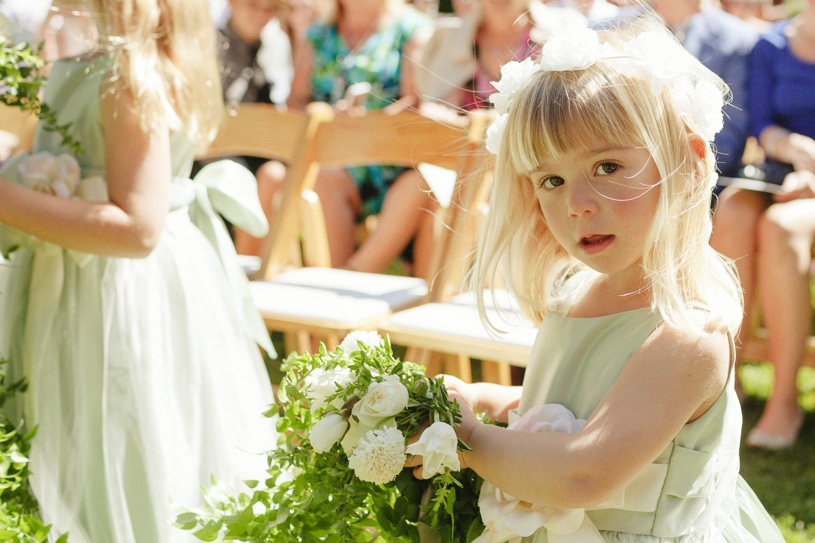 Flower girl with white rose flower crown walking to the aisle at a same sex wedding in woodside california by heather elizabeth photography