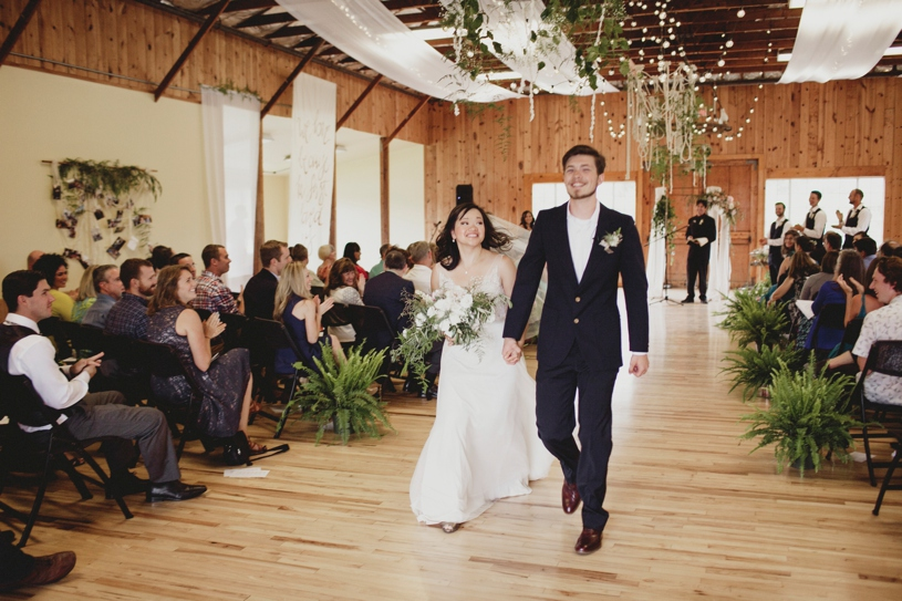 bride and groom leaving their wedding ceremony at the Williams Barn by Heather Elizabeth Photography