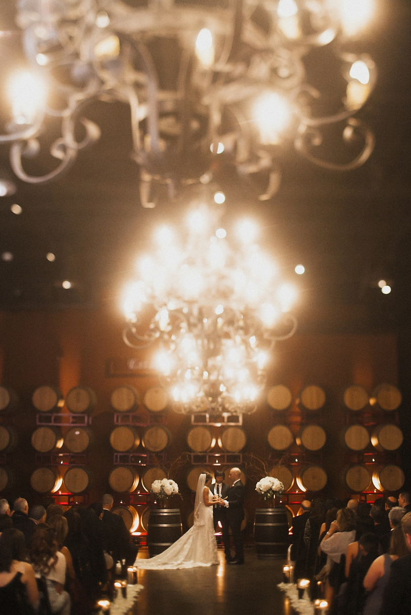 wedding ceremony in the barrel room of the palm event center by Heather Elizabeth Photography