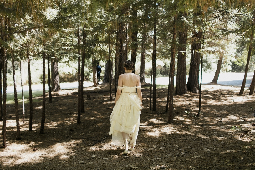 Bride walking to her first look wearing her Sarah Seven dress at the Forest House Lodge by Heather Elizabeth Photography