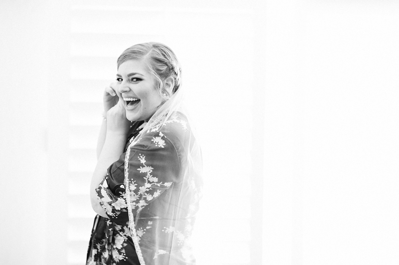 candid artistic image of a bride laughing while she gets read for her wedding day in San Martin California by Heather Elizabeth Photography