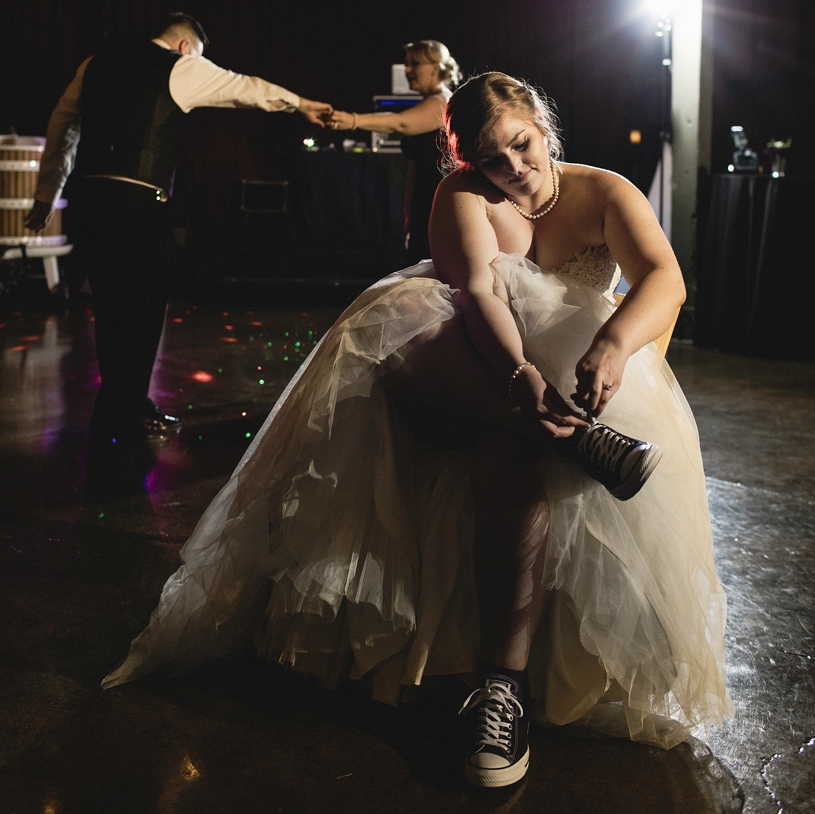 A bride putting on her chuck taylor sneakers for her wedding reception so she can dance at Domenico Winery in San Martin by Heather Elizabeth Photography