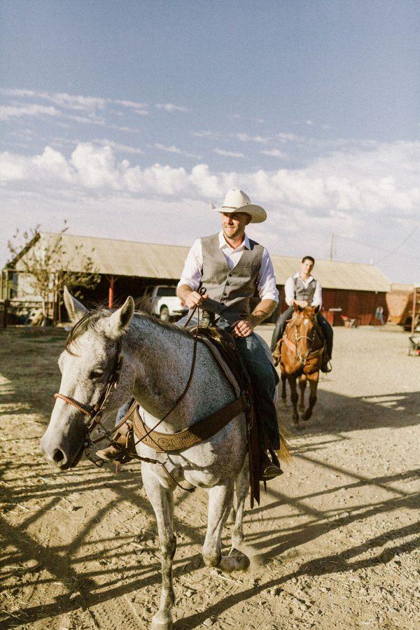 cowboy groom rides a horse into his wedding ceremony in california