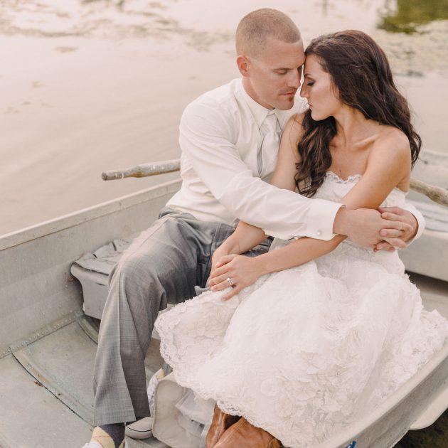 romantic couples portrait in a row boat at Oak Farm Vineyards